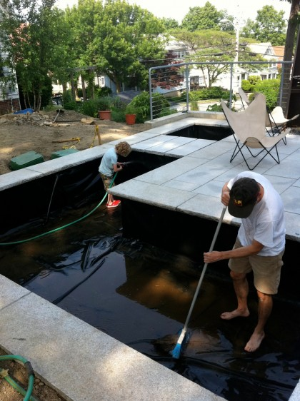 the boys spray down the pond liner