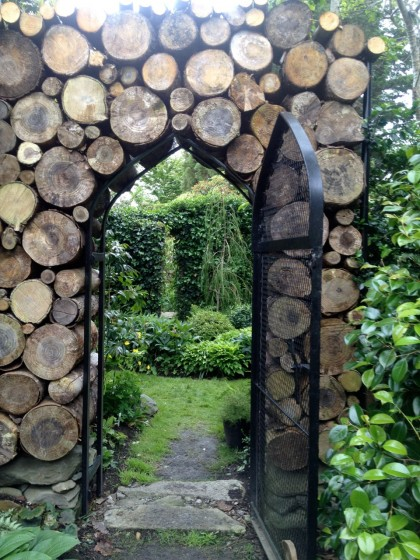 a freshly stacked log wall frames the archway